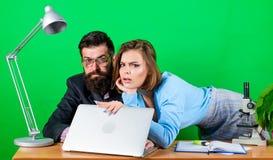 Aislamiento de un reparto trabajo atractivo de la mujer y del hombre en oficina en el ordenador port?til Los ?ticas corporativos  fotos de archivo libres de regalías