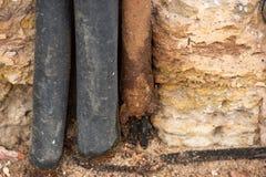 Aislamiento hecho del cable de goma y del tubo oxidado del metal imagen de archivo