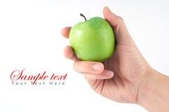 Aislante de la manzana del verde del asimiento de la mano Fotos de archivo libres de regalías