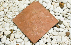 Aislante de piedra de la placa de Brown en la grava blanca Imagenes de archivo