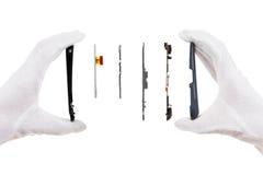 Aislante elegante de los componentes del teléfono en blanco con las manos de un reparador imagenes de archivo