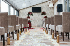 Aisle in the hall between brown chairs with white petals on the Royalty Free Stock Photo