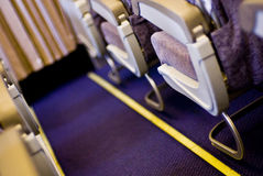 Aisle in plane. The narrow interior aisle of a plane between seats royalty free stock image