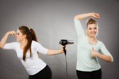 Aisselle de séchage d'amie de femme avec le sèche-cheveux Photos libres de droits