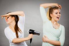 Aisselle de séchage d'amie de femme avec le sèche-cheveux Images stock