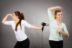Aisselle de séchage d'amie de femme avec le sèche-cheveux Photographie stock
