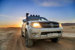 Ait Saoun, Morocco - February 23, 2016: Toyota Hilux on desert during sunset Royalty Free Stock Image
