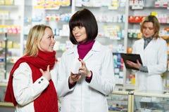 Aiuti del farmacista per drogare acquirente fotografia stock