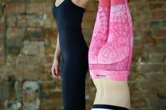 Aiuti dell'istruttore per fare esercizio di yoga su un allungamento Fotografie Stock Libere da Diritti