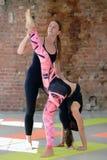 Aiuti dell'istruttore per fare esercizio di yoga su un allungamento Fotografia Stock