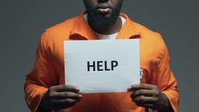 Aiuti la parola su cartone in mani del prigioniero afroamericano, chiedenti la libertà stock footage