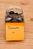 Aiuti prego donando i soldi Fotografie Stock