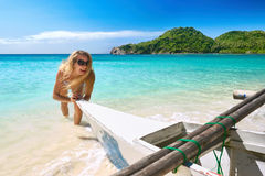 Aiuti sorridenti della giovane donna felice per tirare la barca verso la spiaggia Fotografia Stock