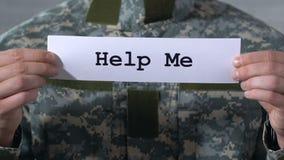 Aiutimi scritto su carta in mani del soldato maschio, riabilitazione dopo la guerra stock footage