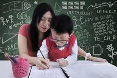Aiuto attraente dell'insegnante un ragazzo da scrivere nella classe Immagine Stock
