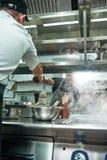 Aiuto in cucina Foto verticale di giovane cuoco unico professionista che dà una smerigliatrice di pepe al suo assistente mentre c immagini stock