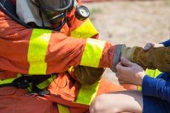 Aiuto del compagno dei pompieri ai guanti d'uso di protezione antincendio fotografie stock libere da diritti