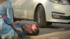 Aiuto della ragazza danneggiato in un uomo di incidente stradale pedone danneggiato negli incidenti stradali archivi video