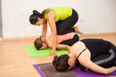 Aiuto dello studente di yoga con una posa Immagini Stock