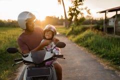Aiuto di papà sua figlia per fissare il casco fotografia stock