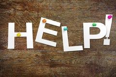 Aiuto di parola tagliato di carta Immagine Stock
