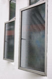 Ajar casement windows with window films. A photo taken on two ajar casement windows installed with window films. Awning windows are installed at the top of the Stock Images