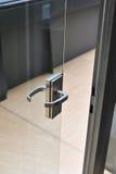Ajar door. Metallic lever on the ajar transparent glass door Stock Image