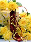 Ajar gift box with yellow flowers is surrounded roses on a white background Royalty Free Stock Images