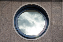 Ajar round window on the tiled granite wall - part of the urban Royalty Free Stock Photos