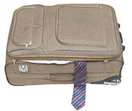 Ajar textile suitcase with male tie isolated Stock Image