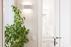 Ajar white door in the bright bathroom. Series switch and modern Royalty Free Stock Photos