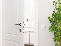 Ajar white door to the bathroom. Series switch on a light gray w Royalty Free Stock Photos