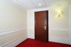 Ajar wooden door, red carpet on floor. And lights on wall in hotel Stock Photos