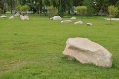 Ajardinando no jardim, as pedras brancas encontram-se no gramado verde Imagens de Stock Royalty Free