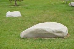 Ajardinando no jardim, as pedras brancas encontram-se no gramado verde Imagens de Stock