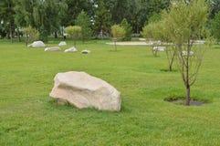 Ajardinando no jardim, as pedras brancas encontram-se no gramado verde Imagem de Stock Royalty Free