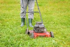Ajardinando o trabalhador que empurra o lawnmower no gramado Foto de Stock