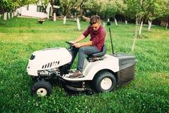 Ajardinando os detalhes - gramado de sega com as ferramentas profissionais no jardim Foto de Stock Royalty Free