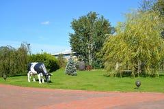 Ajardinar com uma escultura da vaca pastada Fotos de Stock Royalty Free