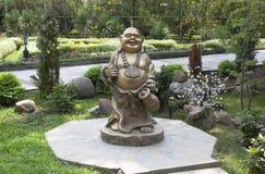 Ajardinar do indivíduo do verde do sanatório Escultura do deus da felicidade Hotei Foto de Stock Royalty Free