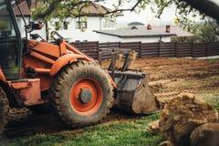 ajardinar industrial resistente da escavadora e terra movente no jardim Imagem de Stock Royalty Free
