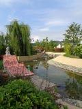 Ajardinar original no parque temático, na lagoa decorativa, nas árvores verdes e nos arbustos, parque de Sochi, Rússia Fotos de Stock