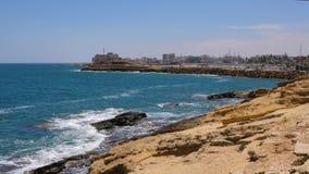 Ajardine as ondas de água que espirram no mar azul e na costa rochosa no fundo da cidade vídeos de arquivo