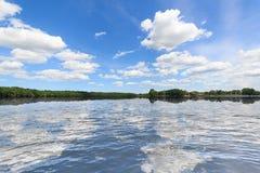 Ajardine, céu azul, nuvens e reflexão da água Imagem de Stock Royalty Free