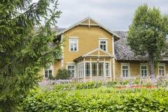 Ajardine a casa de madeira velha do fundo no parque de Turaida Foto de Stock Royalty Free