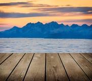 Ajardine a cena do monte do inverno com névoa e esvazie a tabela de madeira da plataforma. Foto de Stock