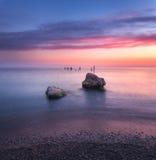 Ajardine com água azul, as pedras e o céu colorido Foto de Stock