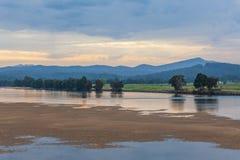 Ajardine com água e as montanhas rasas do lago no crepúsculo Fotografia de Stock Royalty Free