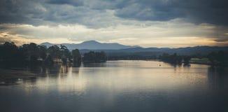 Ajardine com água e as montanhas rasas do lago no crepúsculo A imagem tem o olhar análogo imagem de stock royalty free