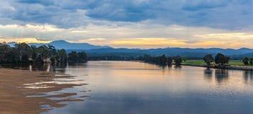 Ajardine com água e as montanhas rasas do lago no crepúsculo com reflexões bonitas Imagem de Stock Royalty Free